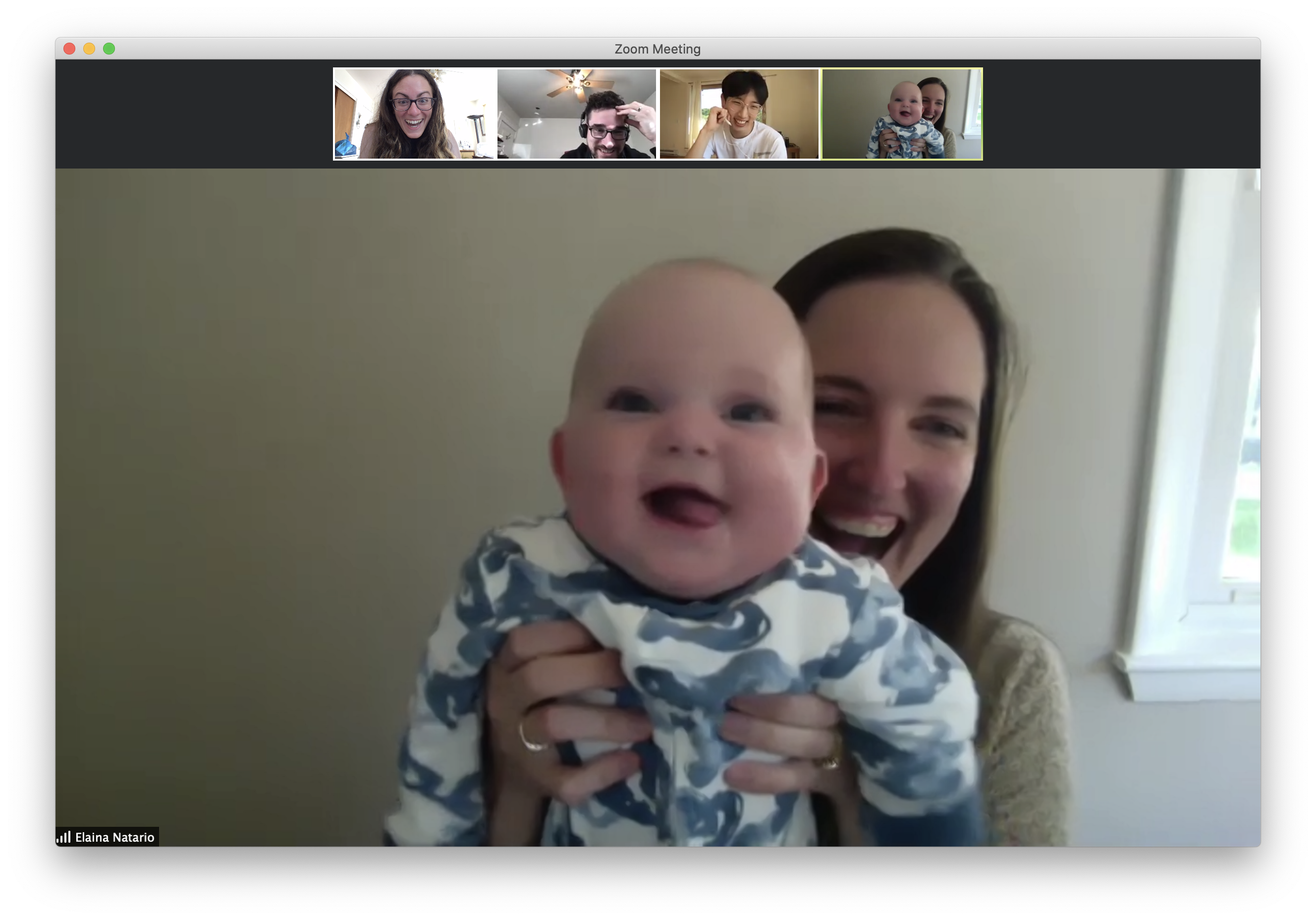 A screen capture of a video meeting on Zoom. There are four small screens at the top, each with a person making a funny face. The large central photo at the bottom is a woman smiling holding up a baby who is also smiling.