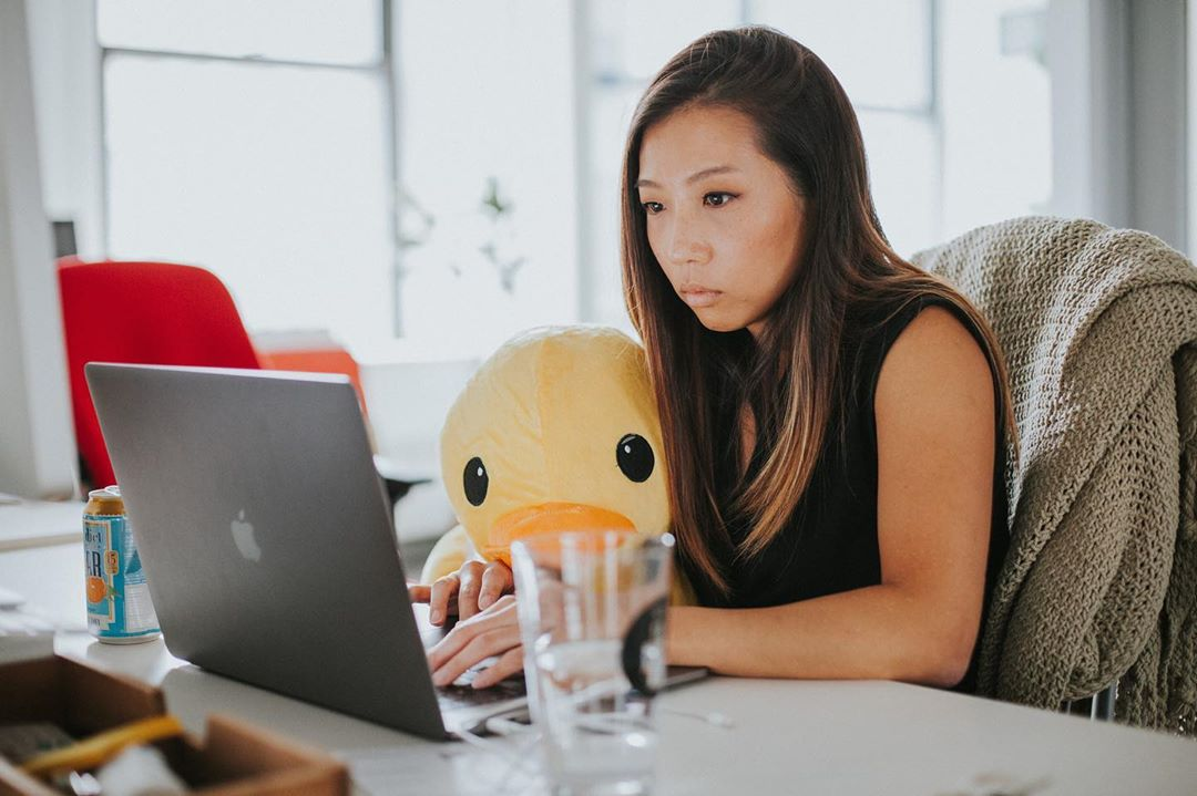 A woman holding an oversized plush duck sitting at a desk in an office, looking at a laptop.