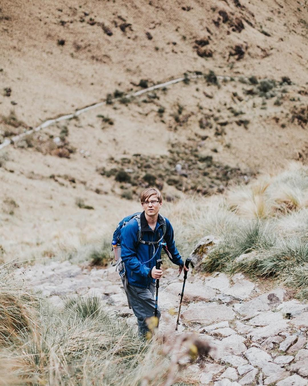 A man in a blue jacket and hiking gear looking to the side on a mountain path.