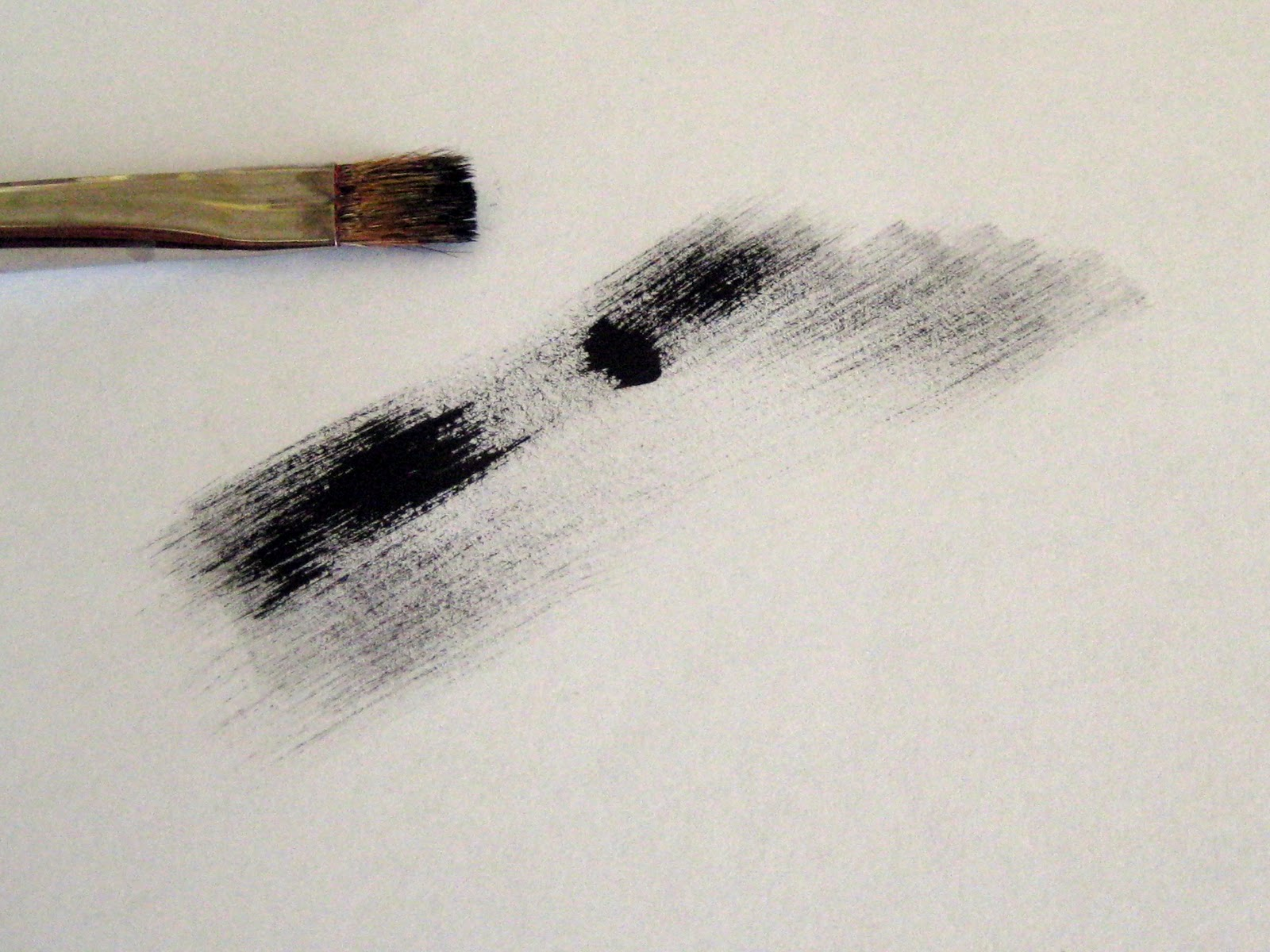 A brush next to paper showing how the paint has been nearly wiped clean.