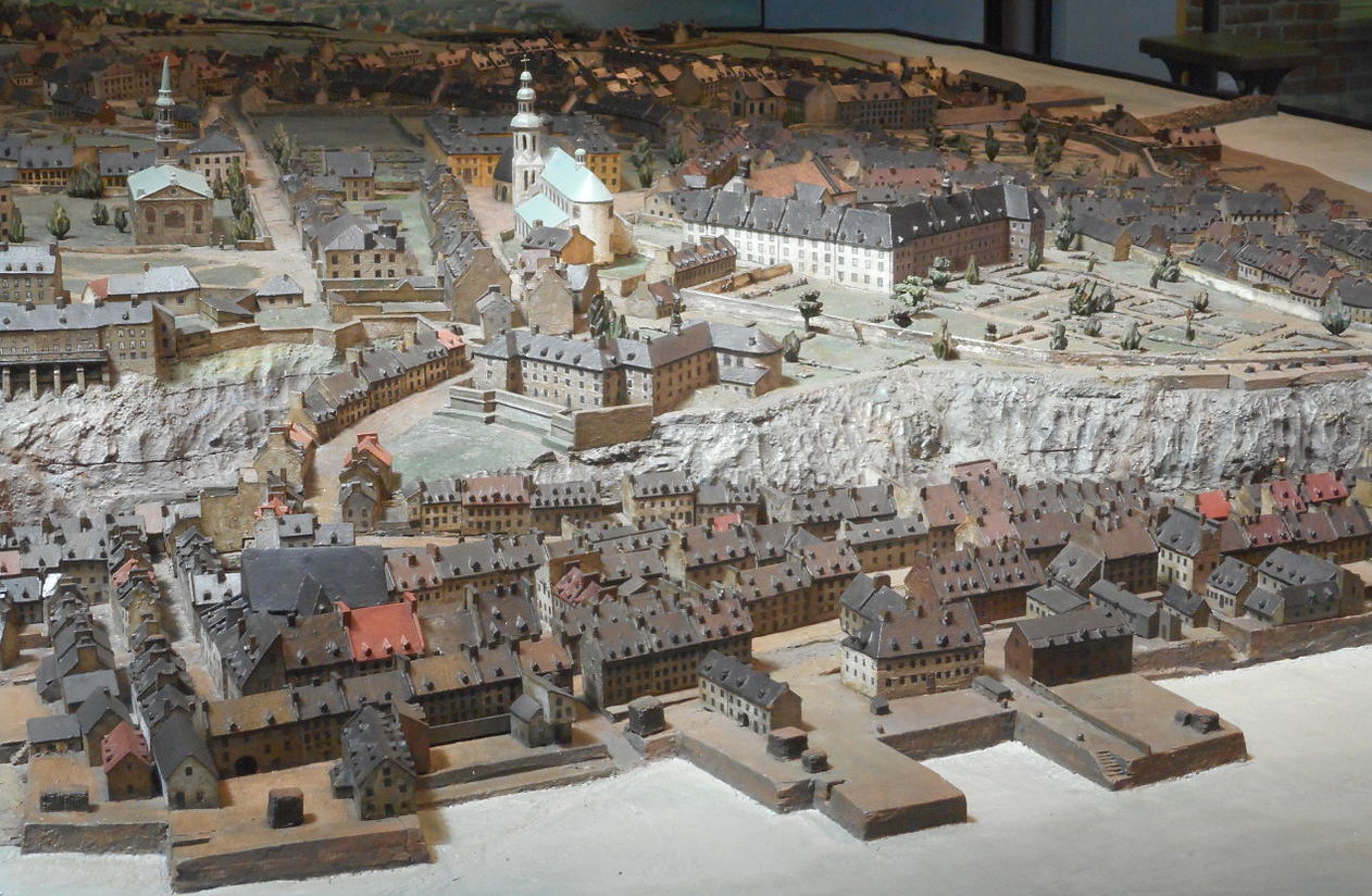 Photo of a scale model of an 18th century city. In the foreground are     some docks along a river and the lower town containing many row-houses.     Towering above the lower town on top of a large bluff is the upper town,     surrounded by stone walls. Two large churches feature prominently. In the     background, farmland can be seen stretching away to the horizon.